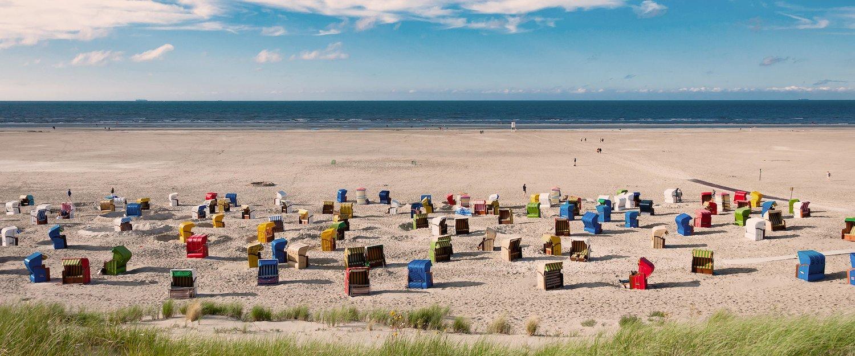 Kleurrijke strandstoelen achter het duinlandschap