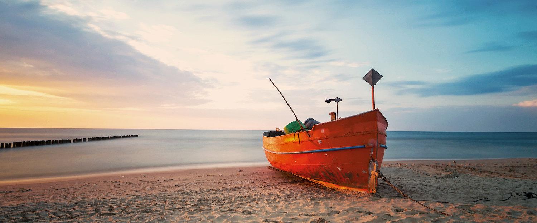 Barca arenata in riva al mare.