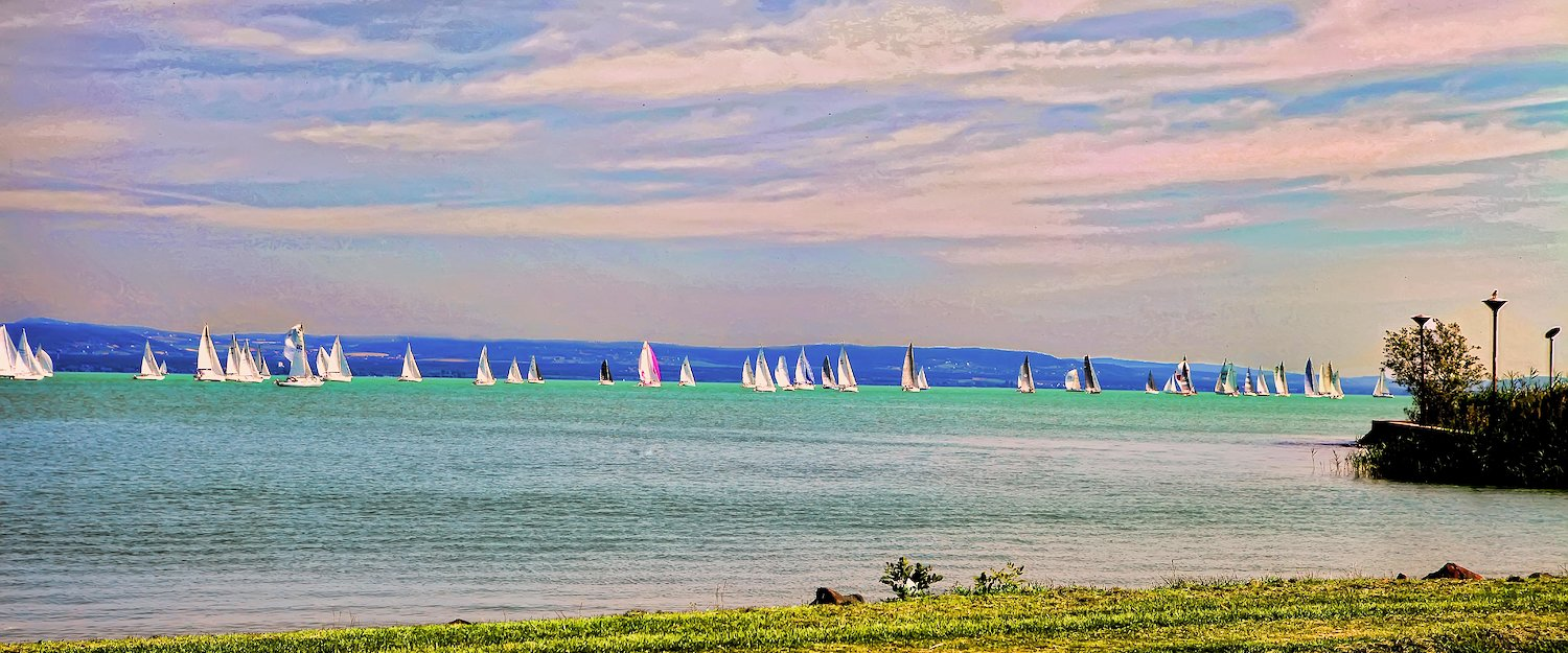 Lake Balaton bathed in evening light, with sailing boats