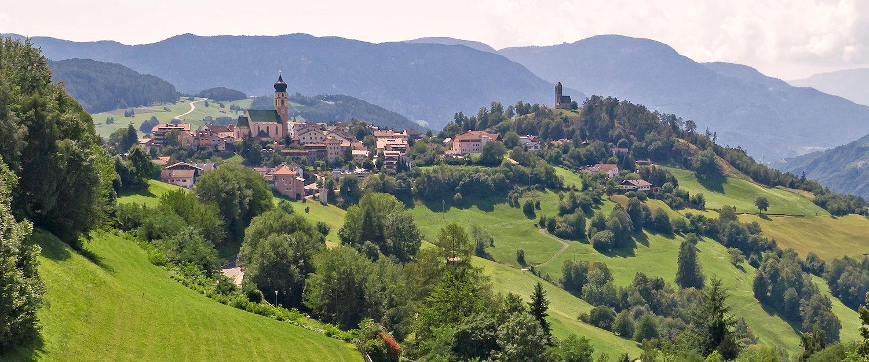 Panorama von Völs am Schlern mit italienischen Alpen-Dolomiten im Hintergrund