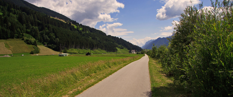 Landstraße in grüner Landschaft im Pustertal